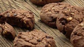 Chocoladekoekjes op houten lijst Gestapelde chocoladeschilferkoekjes geschotene close-up Chocolade Chip Cookies Zoete koekjes stock footage