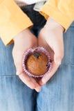 Chocolademuffins met rozijnen in de handen van een kind Stock Afbeeldingen