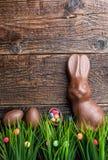 Chocoladepaashaas, eieren en snoepjes op rustieke achtergrond Royalty-vrije Stock Afbeelding