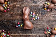 Chocoladepaashaas, eieren en snoepjes op rustieke achtergrond Royalty-vrije Stock Foto's