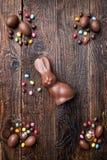 Chocoladepaashaas, eieren en snoepjes op rustieke achtergrond Royalty-vrije Stock Afbeeldingen