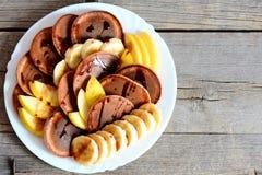 Chocoladepannekoeken met vers fruit Gebakken chocoladepannekoeken met stroop, gesneden bananen en appelen op een witte plaat Royalty-vrije Stock Afbeelding