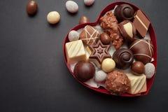 Chocoladepralines in de rode doos van de hartvorm Stock Foto's
