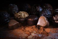 Chocoladepralines en cacaopoeder op rustiek hout als liefdegif Royalty-vrije Stock Afbeeldingen