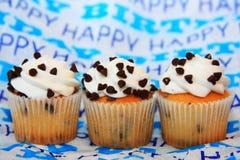 Chocoladeschilfer drie cupcakes op gelukkige verjaardagsachtergrond royalty-vrije stock afbeeldingen