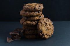 Chocoladeschilferkoekjes en chocoladestukken op donkere achtergrond Royalty-vrije Stock Foto's