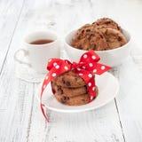 Chocoladeschilferkoekjes op een witte plaat met kop thee Stock Afbeelding