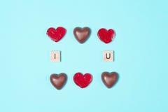 Chocoladesuikergoed en rode lollys met houten brieven Stock Fotografie
