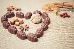 Chocoladesuikergoed met alcoholische drank in vorm van hart op achtergrond Stock Afbeeldingen