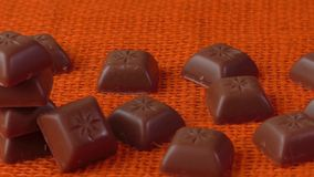 Chocoladesuikergoed over oranje achtergrond stock video