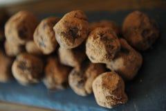 Chocoladetruffels in bestrooide cacao Op de leiraad op houten achtergrond Close-up, textuur stock fotografie