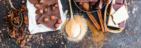 Chocolat和香料在黑桌上 免版税库存图片