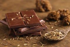 Chocolat amer coupé dans la pile avec des graines de cumin sur le CCB en bois Photographie stock