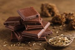 Chocolat amer coupé dans la pile avec des graines de cumin sur le CCB en bois Photos libres de droits