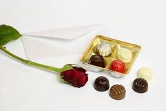 Chocolat avec la rose de lettre et de rouge Photographie stock