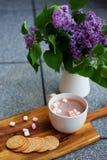 Chocolat chaud avec des guimauves et des biscuits de beurre emboutis faits maison à côté du lilas Photographie stock libre de droits