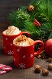 Chocolat chaud avec la crème fouettée dans des tasses rouges Composition de Noël Photographie stock libre de droits