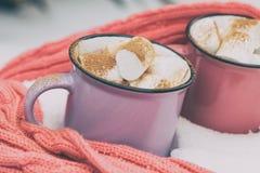 Chocolat chaud avec la guimauve dans deux des tasses roses et violettes de wrapp Image libre de droits