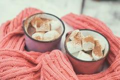 Chocolat chaud avec la guimauve dans deux des tasses roses et violettes de wrapp Photo stock