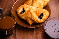 Chocolat chaud avec les petits pains appétissants Confiture de cerise dans un vase en verre Les petits pains doux avec la myrtill photo libre de droits