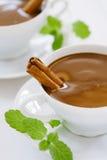 Chocolat chaud dans des cuvettes blanches avec des endroits de lumi?re du soleil Photographie stock