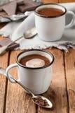Chocolat chaud dans des deux tasses d'émail Images stock
