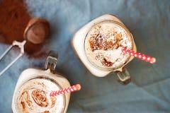Chocolat chaud dense épicé avec de la cannelle et la crème fouettée décorées de la poudre de cacao sur la serviette bleue Images libres de droits
