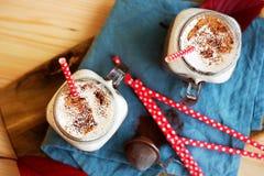 Chocolat chaud dense épicé avec de la cannelle et la crème fouettée décorées de la poudre de cacao sur la serviette bleue Photographie stock