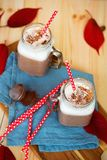 Chocolat chaud dense épicé avec de la cannelle et la crème fouettée décorées de la poudre de cacao sur la serviette bleue Images stock