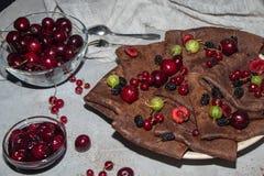 Chocolat, crêpes rondes minces préparées avec de la confiture de cerise image stock