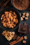 Chocolat, écrous, bonbons, épices et sucre roux Photographie stock libre de droits