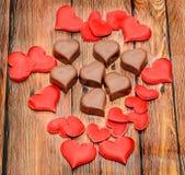 Chocolat de forme de coeur avec les coeurs rouges, bonbons à jour de valentines, fond en bois Image stock