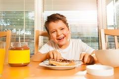 Chocolat de propagation de garçon heureux sur son pain grillé Photos stock