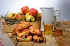 Chocolat del au de los cruasanes y de los dolores con una caja de manzanas Imagen de archivo libre de regalías