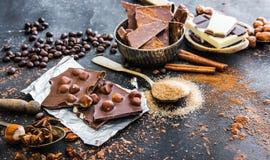 Chocolat e especiarias na tabela preta Imagem de Stock Royalty Free