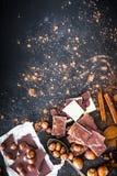 Chocolat e spezie sulla tavola nera Fotografie Stock
