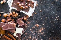 Chocolat e spezie sulla tavola nera Fotografia Stock