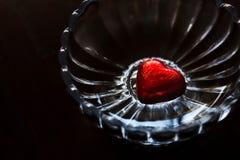 Chocolat en forme de coeur d'amour enveloppé dans l'aluminium rouge dans le bol en verre Photo stock