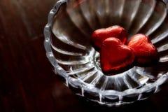 Chocolat en forme de coeur d'amour enveloppé dans l'aluminium rouge dans le bol en verre Photos stock