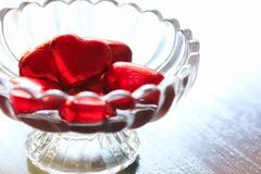 Chocolat en forme de coeur d'amour enveloppé dans l'aluminium rouge dans le bol en verre Image stock