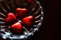 Chocolat en forme de coeur d'amour enveloppé dans l'aluminium rouge dans le bol en verre Photographie stock