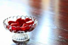 Chocolat en forme de coeur d'amour enveloppé dans l'aluminium rouge dans le bol en verre Photo libre de droits