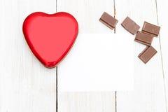 Chocolat et coeur rouge sur un fond en bois blanc Configuration plate Photographie stock