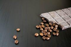 Chocolat et grains de café foncés sur la vieille table en bois Images libres de droits