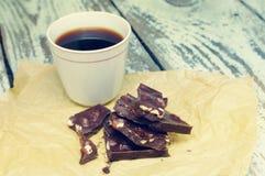 Chocolat foncé avec des écrous et une tasse de café noir sur le papier chiffonné Photographie stock libre de droits