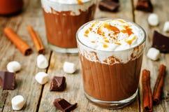Chocolat foncé chaud avec la crème fouettée, la cannelle et le caram salé Photographie stock libre de droits