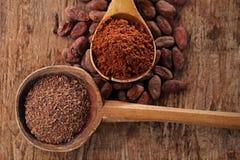 Chocolat foncé râpé dans la vieille cuillère en bois sur le choco rôti de cacao Photo libre de droits