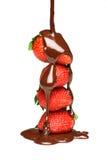 Chocolat fondu pleuvant à torrents au-dessus des fraises Photos stock