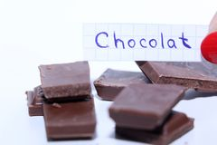Chocolat, French word for the English Chocolate word. Learn new language, French word for Chocolate written on a note near some chocolate. White background Royalty Free Stock Photos