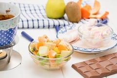 Chocolat, guimauves, pomme, mandarine, kiwi et banane de fondue Photographie stock